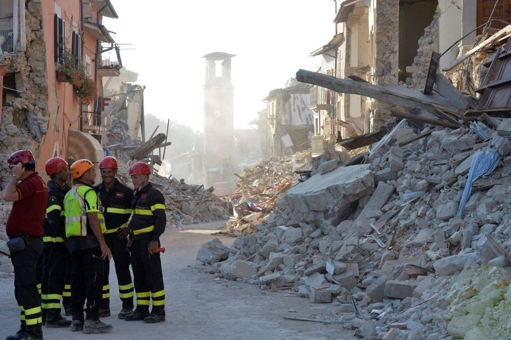 Firefighters and rescue workers stand near the damaged Santu2019Agostino church (C) and rubble and debris of damaged buildings.