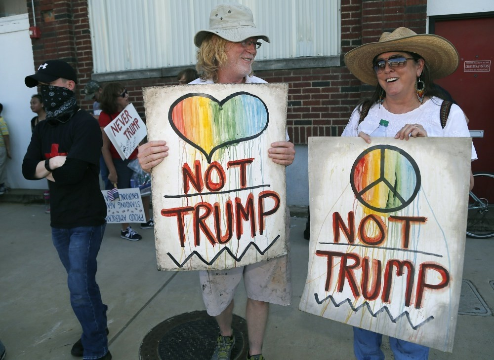 Dallas residents David Lyles (L) and Cynthia Seely (R) holding protest signs on Lamar Street outside a rally for Republican presidential candidate Donald Trump at Gilley's on June 16, 2016 in Dallas.