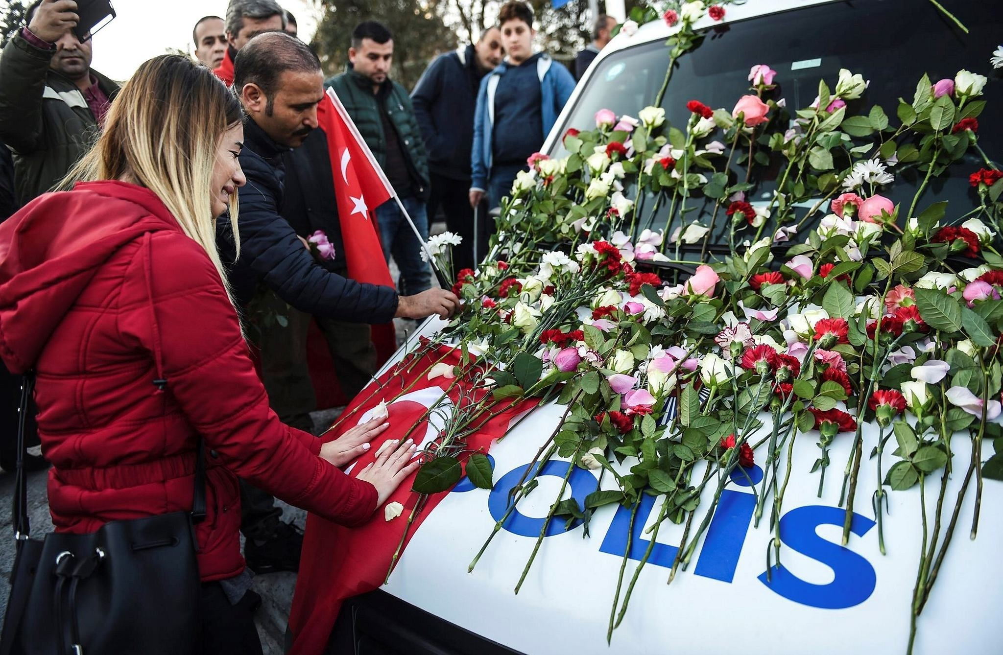 A woman cries next to a police car at the scene of the attack covered with flowers left by mourners. The public marched on Sunday against terror and to remember the victims.