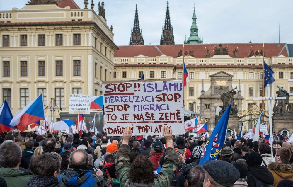 A protester holding up a sign written in Czech that reads, ,Stop Islam and stop Merkel,, during an anti-Islam rally in front of the Prague Castle in Prague, Czech Republic, Feb. 6, 2016.