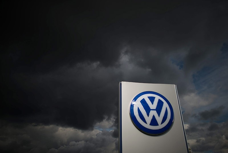 Dark clouds above a corporate logo of German car manufacturer Volkswagen in front of the Volkswagen plant in Wolfsburg, Germany. (EPA Photo)