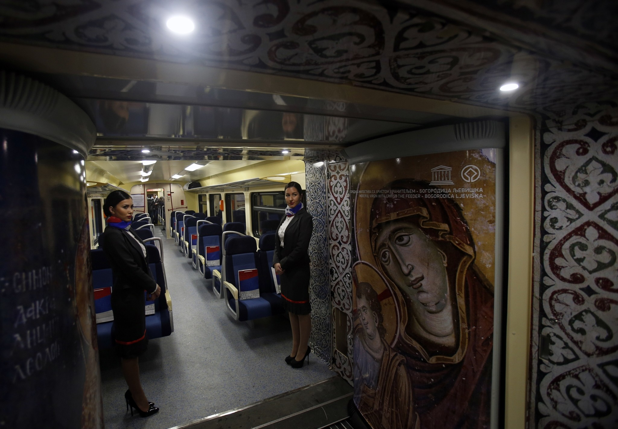 Train hostesses stand in a train carriage decorated with iconic religious figures as it departs from Belgrade to Mitrovica, Kosovo at Belgrade's railway station, Serbia, Saturday, Jan. 14, 2017. (AP Photo)