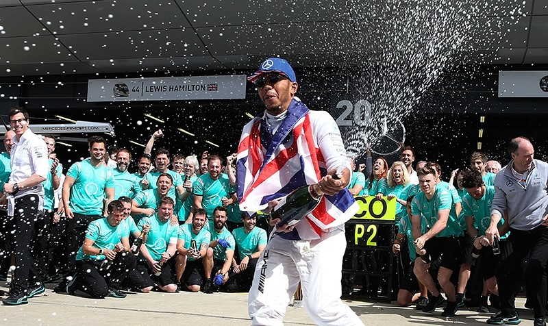 Mercedes driver Lewis Hamilton of Britain celebrates spraying champagne in team garage after winning the British Formula One Grand Prix at the Silverstone racetrack. (AP Photo)