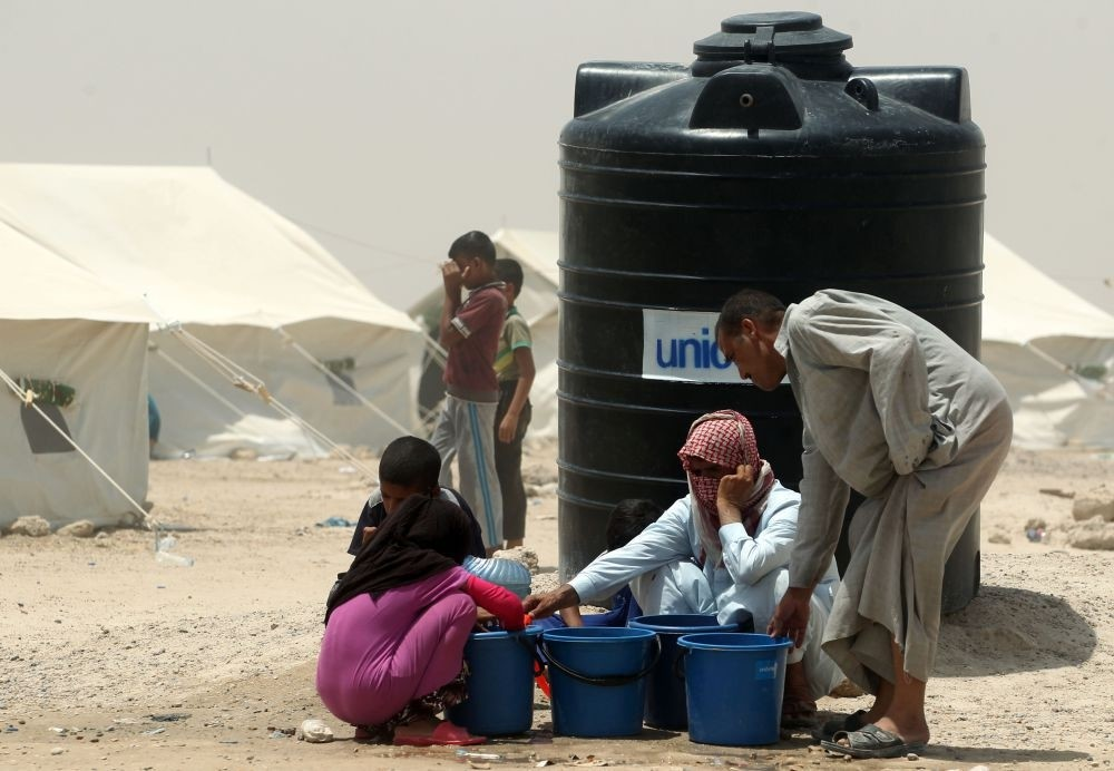 Iraqis displaced from Fallujah gather next to a water tank at a newly opened camp where they are taking shelter in Amriyat al-Fallujah, June 27.