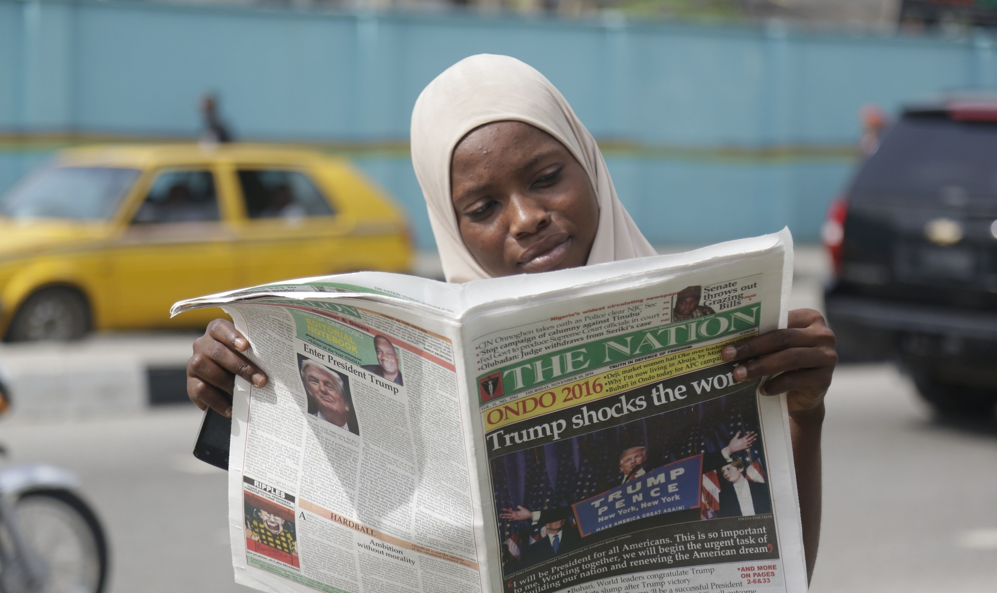 A muslim woman reads a newspapers on a street reporting with headline ,Trump shocks the world, to refer to U.S President-elect Trump's victory in Lagos, Nigeria, Nov. 10, 2016. (AP Photo)