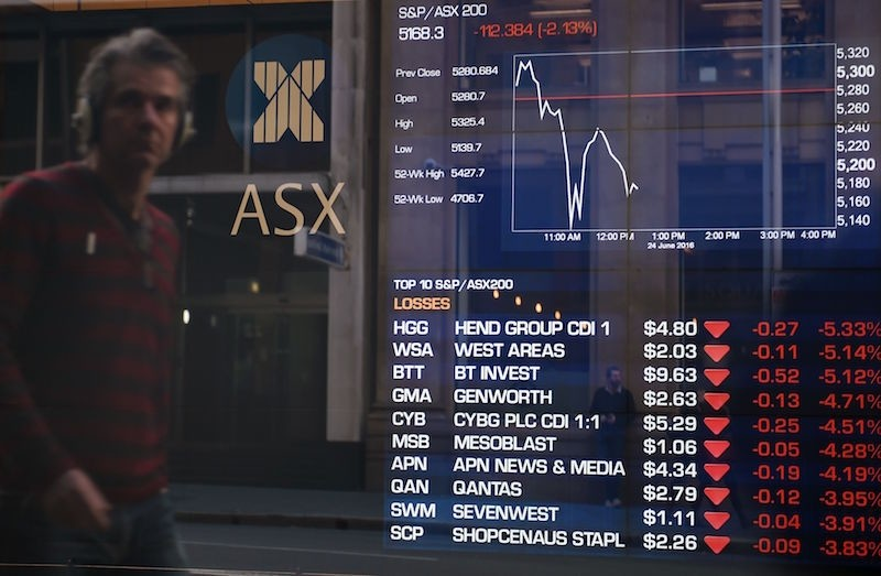 A man looks at the fluctuation in the share prices through a stock exchange window in Sydney on June 24, 2016.  (AFP Photo)