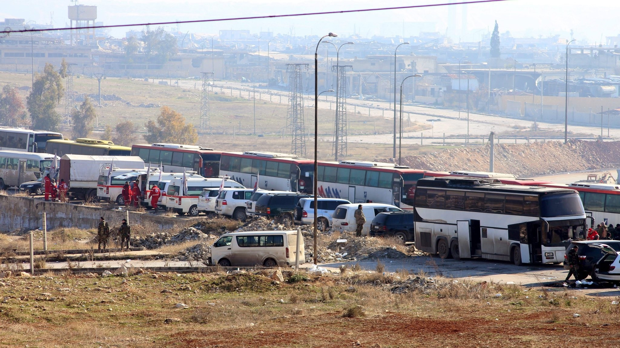 Buses wait to evacuate a group of fighters and their families from eastern neighborhoods of Aleppo, Syria, 19 December 2016. (EPA Photo)