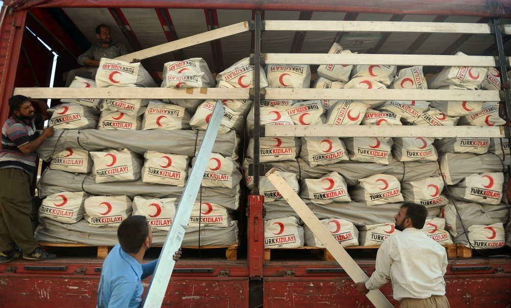 Workers unload aid boxes in Irbil, Iraq. Turkey dispatched 20 trucks of aid for the displaced in the country.