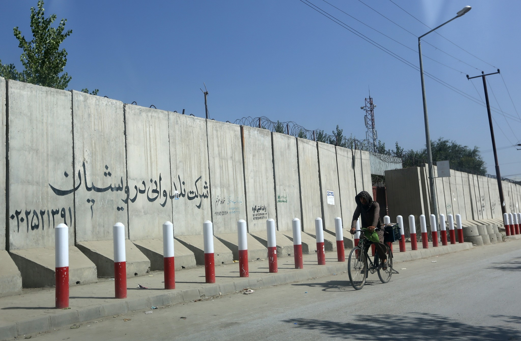 An Afghan man pedals his bicycle past American University of Afghanistan in Kabul, Afghanistan, Monday, Aug. 8, 2016. (AP Photo)