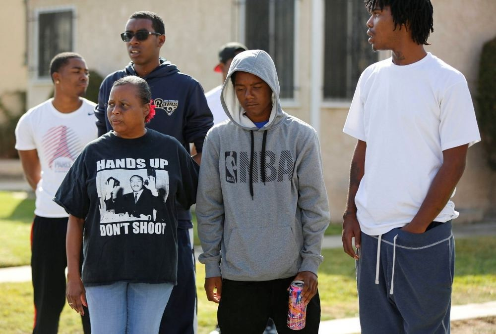 After a fatal shooting in L.A., neighbors and members of the community gather around a makeshift memorial on Oct. 2.