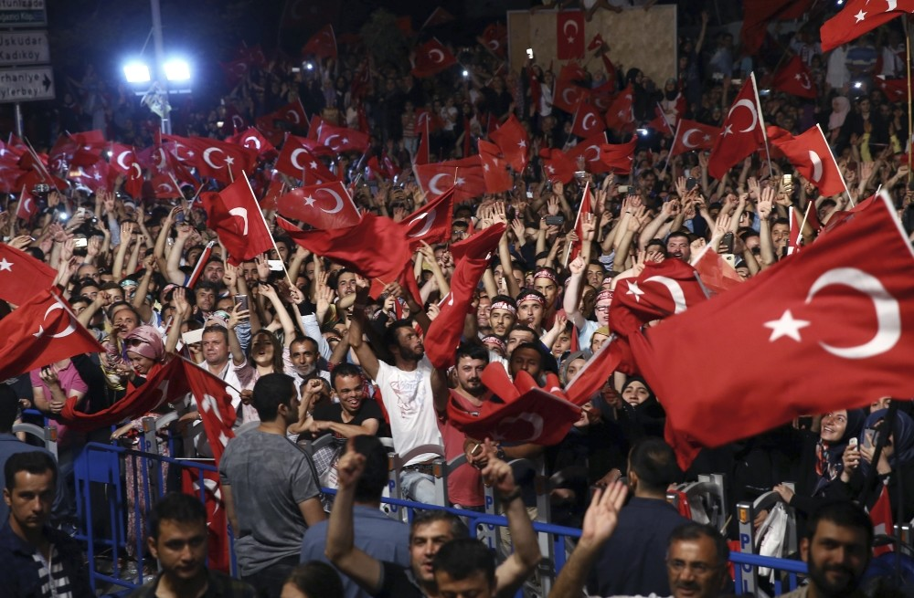 People listening to President Erdou011fan as he addresses them in front of his residence in Istanbul, July 19.