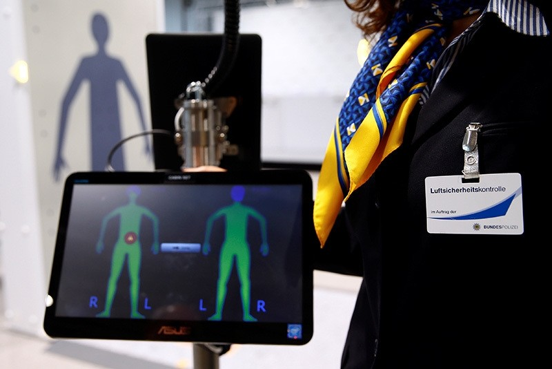 An employee of a private security firm at the Cologne-Bonn Konrad Adenauer Airport demonstrates a full-body scan at the world's pilot innovative ,Easy Security, system for passengers in Cologne (Reuters Photo)