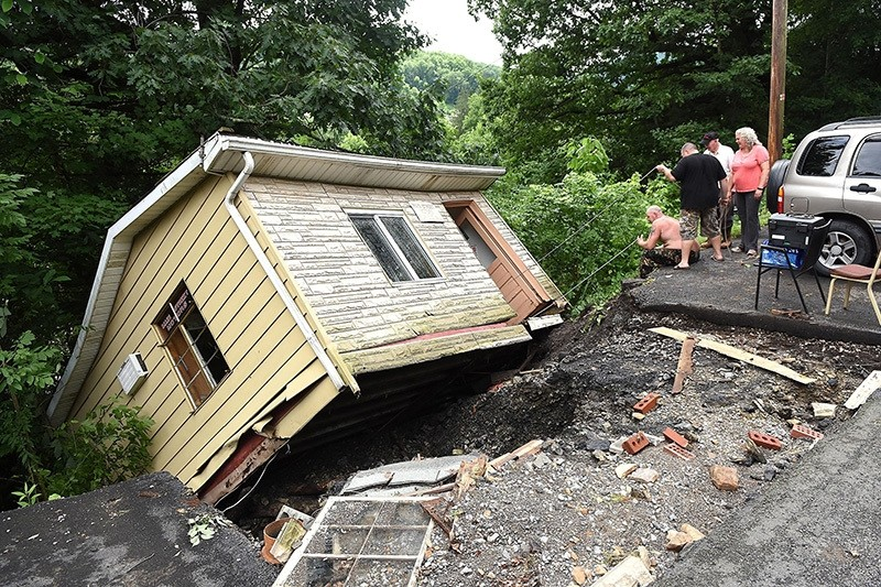 Employees and volunteers with Main Street Motors attempt to get company documents out of the building Friday June 24, 2016, in Richwood, W.Va., after the company's building was knocked off its foundation by extensive flooding. (AP Photo)
