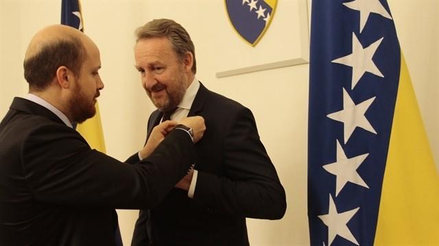 Bilal Erdou011fan (L) pins a badge on member of the presidency of Bosnia and Herzegovina Bakir Izetbegovic's suit, in Sarajevo, on May 27, 2015