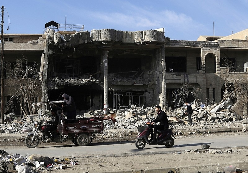 People pass by damaged and destroyed houses after fighting between Iraqi security forces and Daesh terrorists in a recently liberated neighborhood (AP Photo)