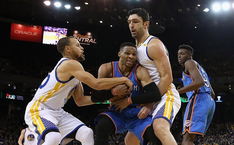 Russell Westbrook #0 of the Oklahoma City Thunder is guarded by Stephen Curry #30 and Zaza Pachulia #27 of the Golden State Warriors at ORACLE Arena on January 18, 2017 in Oakland, California. (AFP Photo)