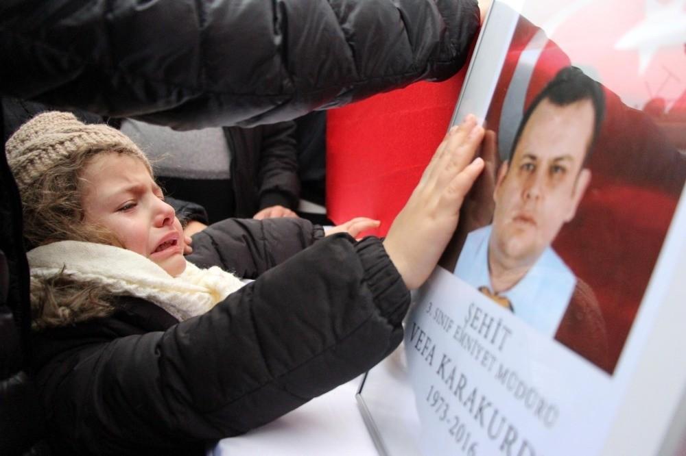 Six-year-old Duru Karakurdu cries while touching the photo of her father Vefa Karakurdu, veteran police chief died in the blasts.