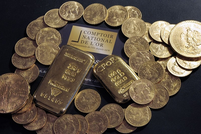This file photo taken on October 05, 2012 shows Gold bars and coins displayed on a table at the Comptoir National de l'Or, a shop that buys, sales and estimates gold and jewellery in Paris. (AFP Photo)