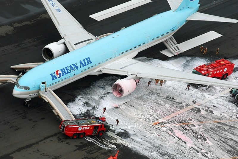 An aerial picture shows firefighters spraying foam at the engine of a Korean Air Lines plane after smoke rose from it at Haneda airport in Tokyo, Japan, May 27, 2016. (Kyodo Photo via Reuters)