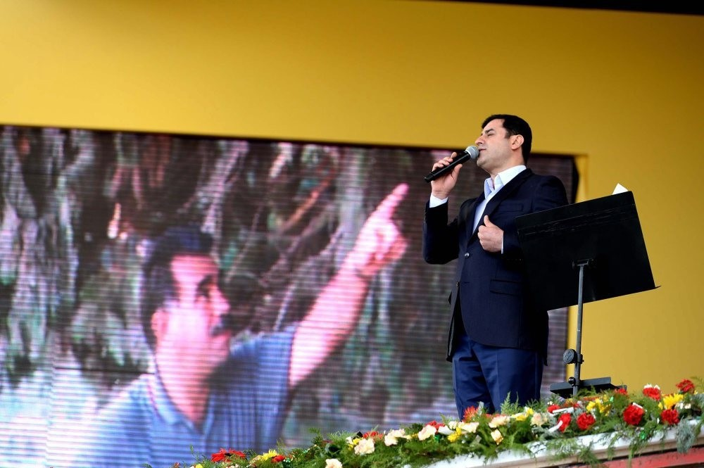 Demirtau015f gives a speech in front of an image of PKK leader u00d6calan