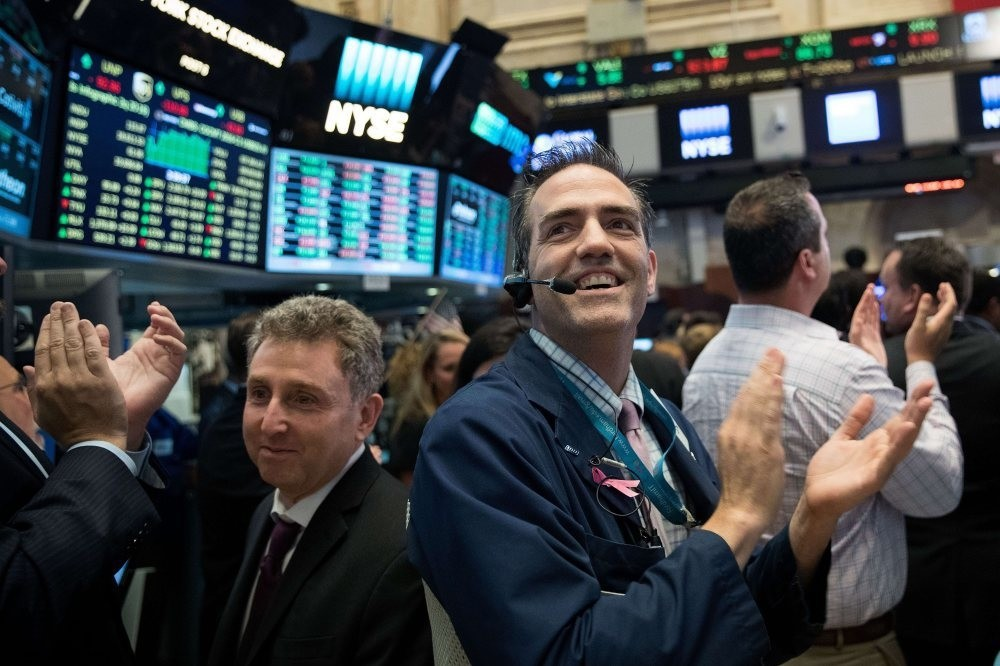 Traders applaud as the closing bell rings on the floor of New York Stock Exchange (NYSE)