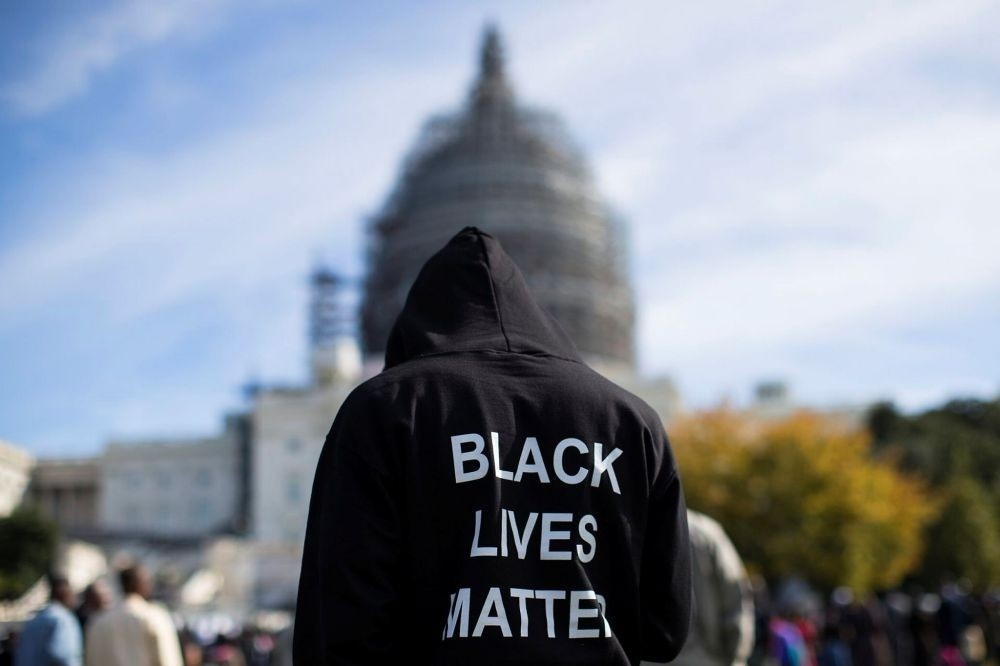 A man wears a hoodie that reads, ,Black Lives Matter, standing on the lawn of the Capitol building on Capitol Hill in Washington during a rally to mark the 20th anniversary of the Million Man March. (AP Photo)