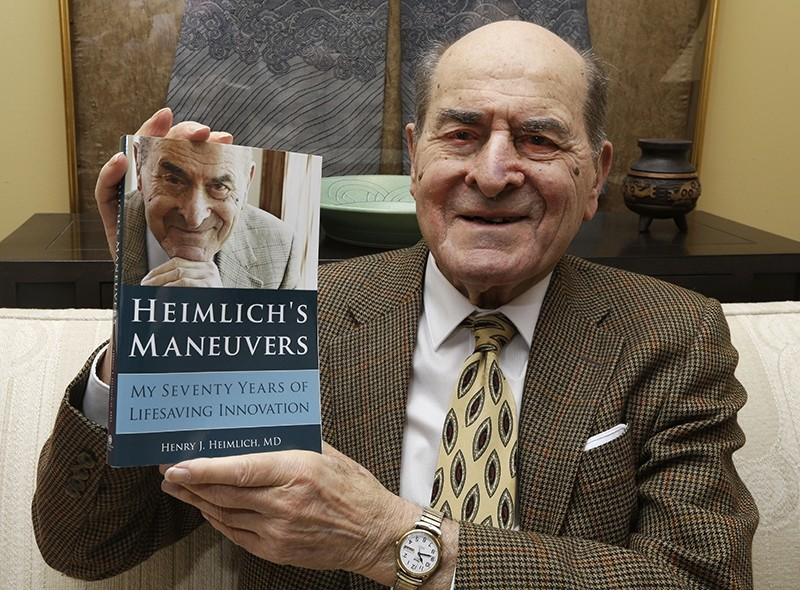 In this Feb. 5, 2014, file photo, Dr. Henry Heimlich holds his memoir prior to being interviewed at his home in Cincinnati. (AP Photo)
