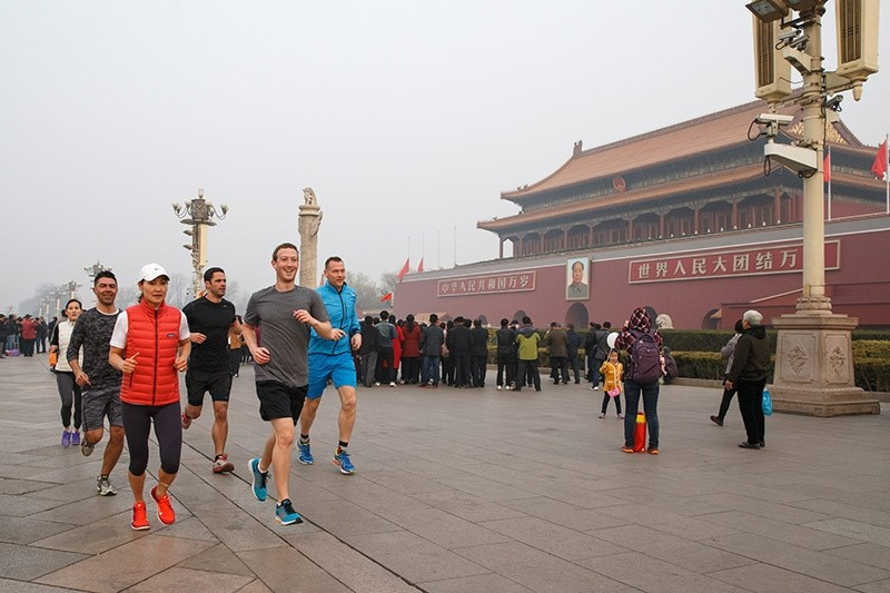 This handout picture taken and provided by Facebook on March 18, 2016, shows Facebook CEO Mark Zuckerberg (front R, grey shirt) running past Tiananmen Gate, the entrance to the Forbidden City, in Beijing. (AFP Photo)