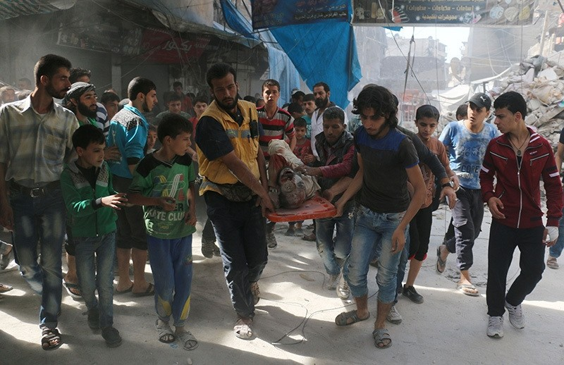 Syrians carry the body of a man following air strikes on the rebel-held Fardous neighbourhood of the northern embattled Syrian city of Aleppo on October 12, 2016