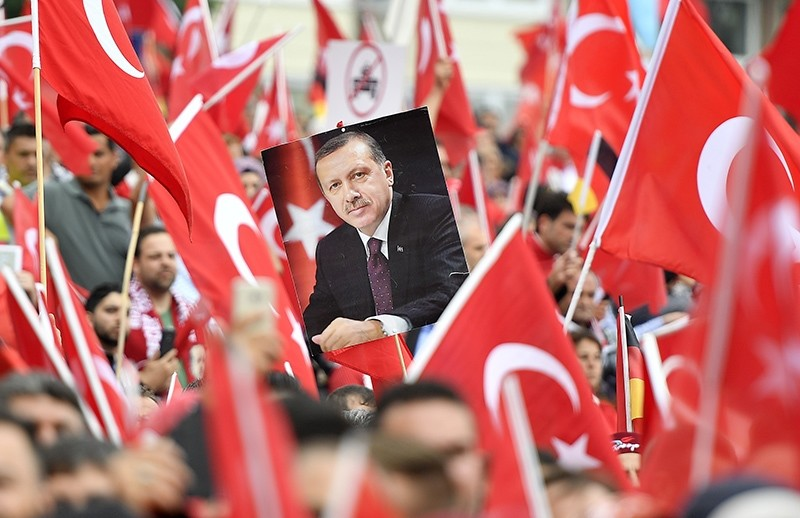 A picture of President Erdou011fan is framed by national flags during a demonstration in Cologne, Germany (AP Photo)