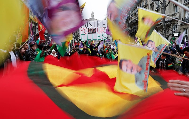 PKK supporters hold flags which portray Abdullah u00d6calan, leader of the terror group. (Reuters Photo)