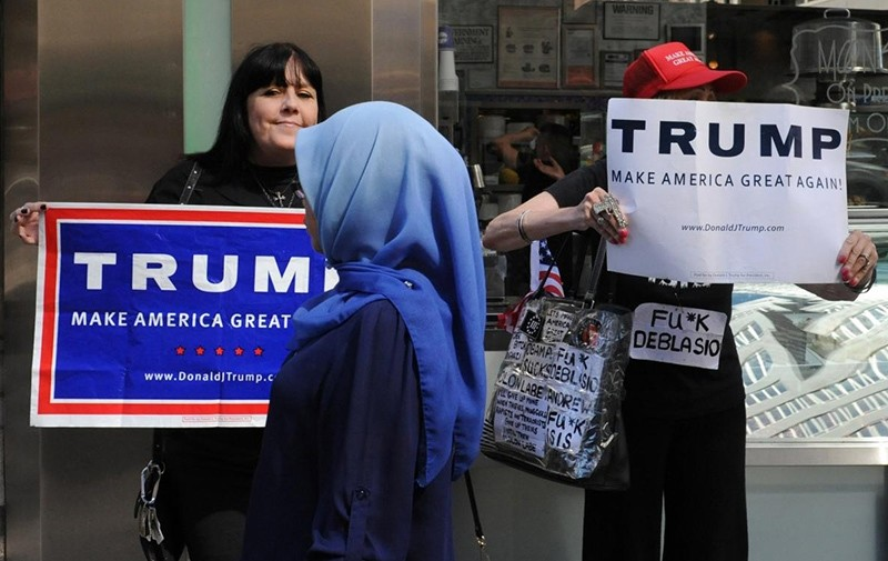 A woman wearing a Muslim headscarf walks past people holding U.S. Republican presidential nominee Donald Trump (Reuters Photo)