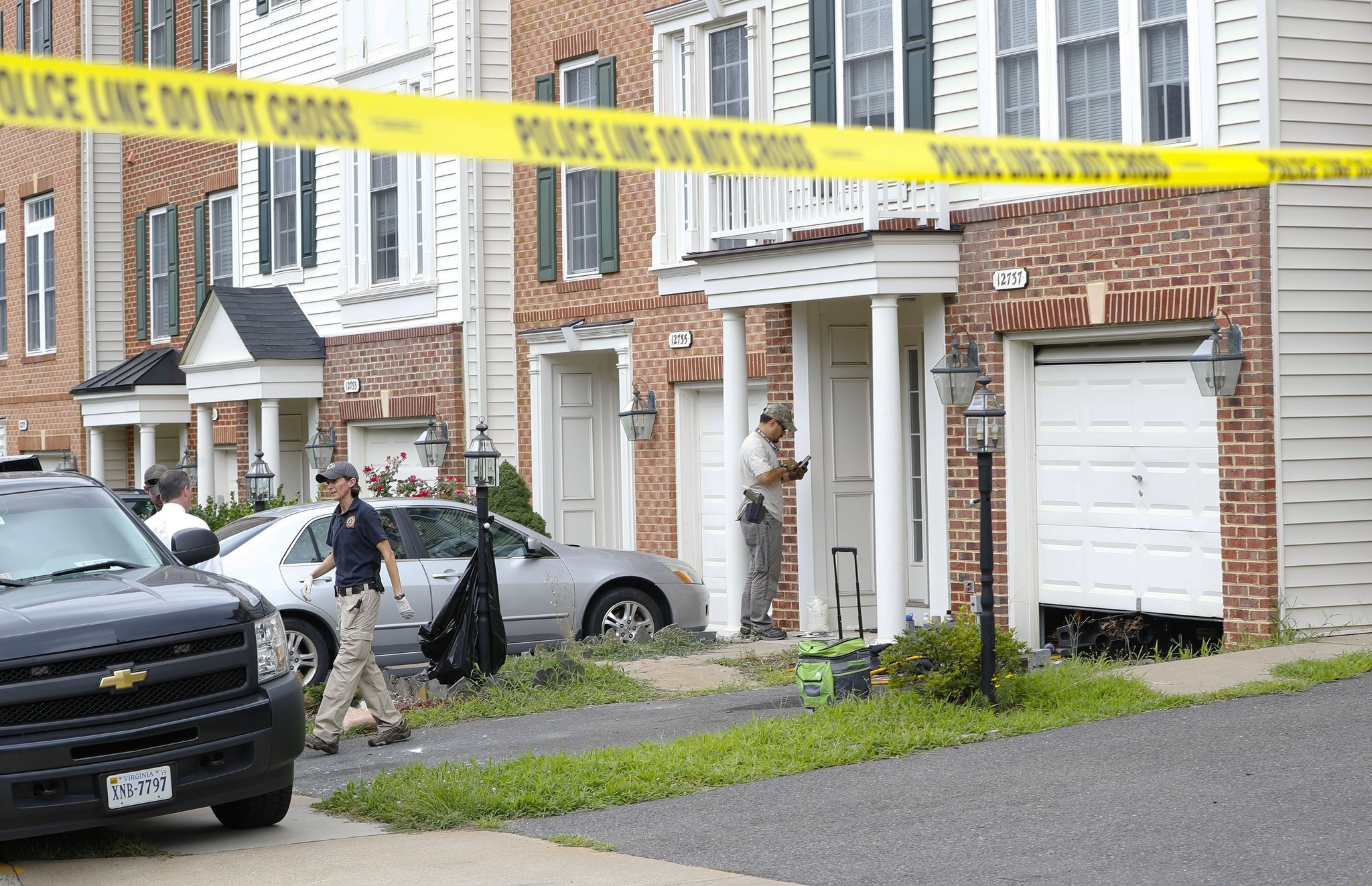 Law enforcement officers are seen outside the home of Nicholas Young, a Washington Metro Transit Officer, Wednesday, Aug. 3, 2016, in Fairfax, Va. (AP Photo)
