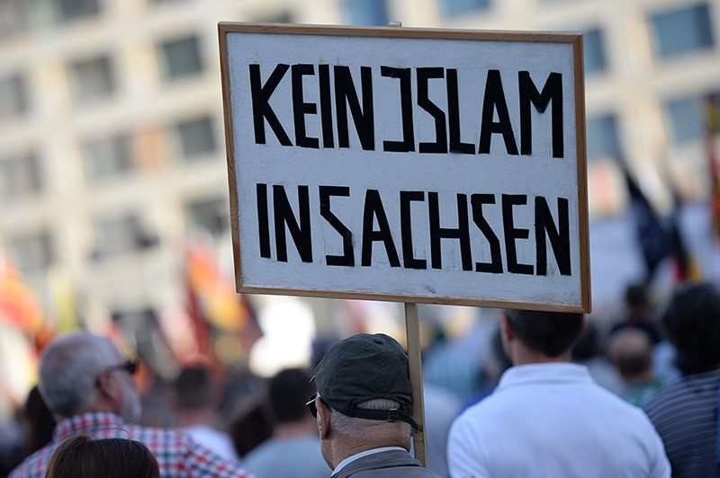A participant carries a placard reading; 'No Islam in Saxony', during PEGIDA rally in Dresden, Germany, 30 May 2016. (EPA)