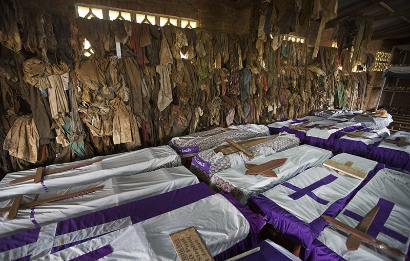 Clothes of some people slaughtered whilst seeking refuge inside the church hang above coffins containing the remains of victims killed in and around the Catholic church during the 1994 genocide in Ntarama, Rwanda. April 2014. (AP Photo)