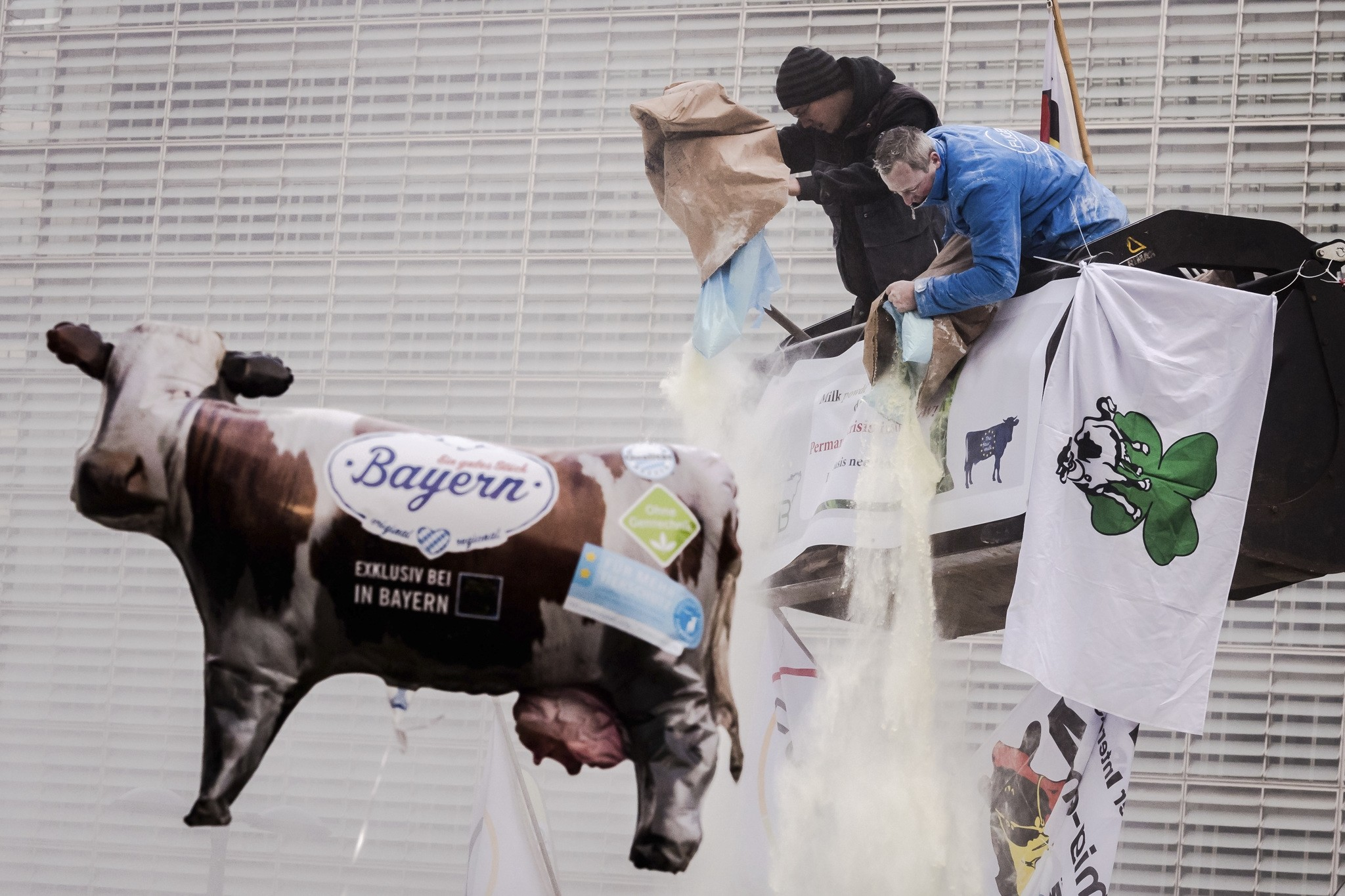 European dairy farmers spray the EU Council building with milk powder to protest the crisis in their sector, in Brussels on Monday, Jan. 23, 2017. (AP Photo)