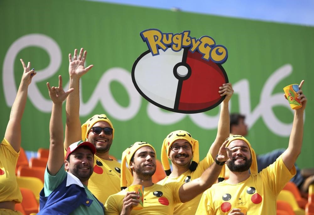Rugby fans dressed as Pikachu from u201cPokemon Gou201d watch from the stands.
