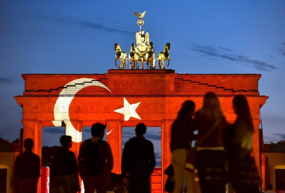 People looking at the Brandenburg Gate onto which a Turkish flag is projected to show a support for Turkey a day after the attacks at Istanbul's International Atatu00fcrk airport, Berlin, June 29, 2016.
