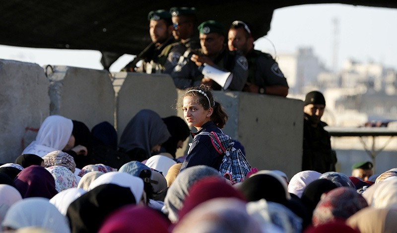 Palestinians wait to cross the Israeli Qalandia checkpoint as Muslim worshippers make their way to attend the second Friday prayer of the holy fasting month of Ramadan in Jerusalem's al-Aqsa mosque compound, on June 17, 2016 (AFP Photo