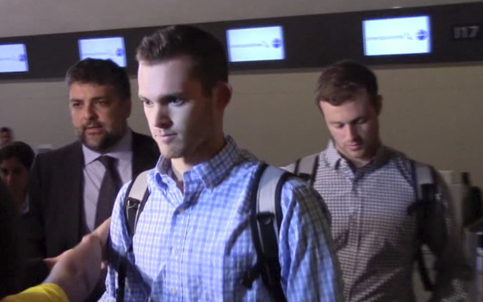 In this image made from video, American Olympic swimmers Gunnar Bentz and Jack Conger walk in the departure area after checking into their flight at the airport in Rio de Janeiro. (AP Photo)