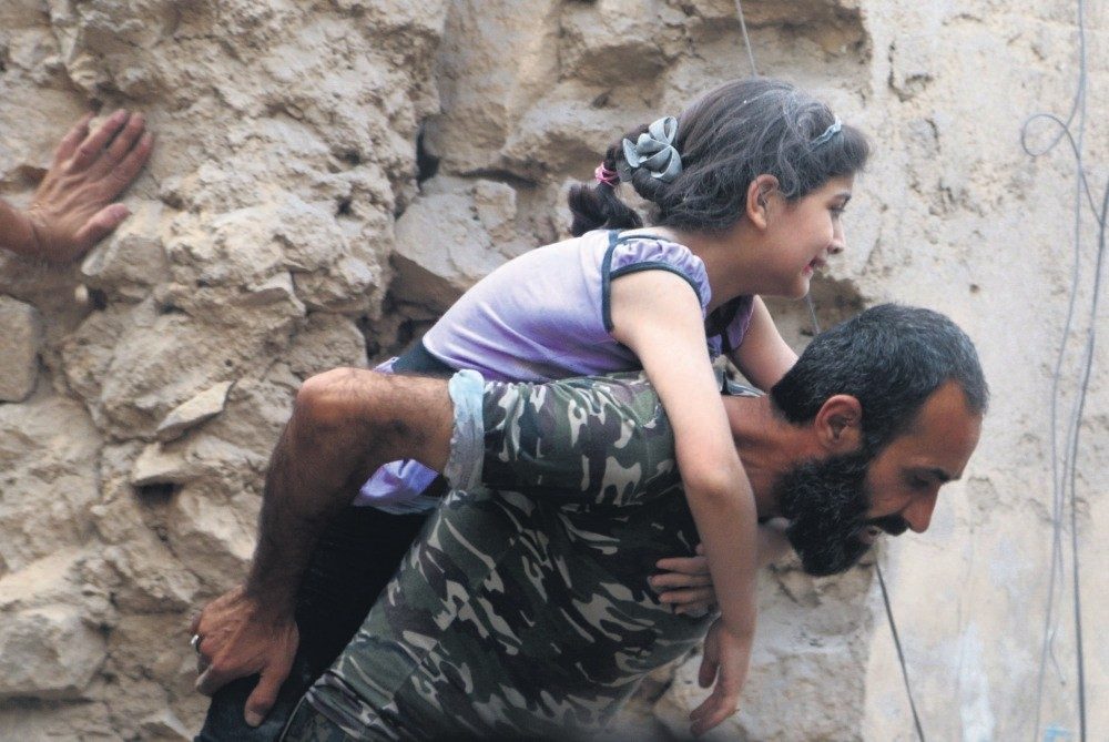 A man carries an injured girl after an airstrike on Aleppo's opposition held Kadi Askar in Aleppo.