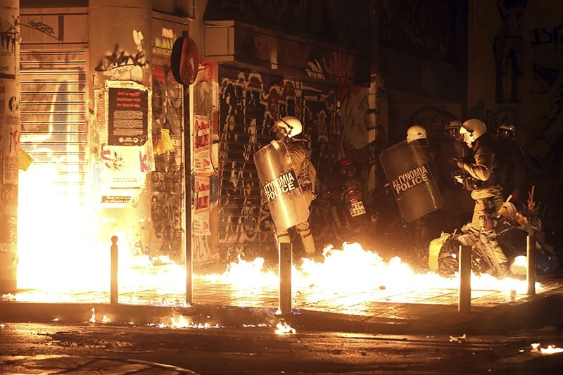 Police officers walk past flames from a fire bomb thrown by demonstrators during a protest against the visit of US President Barack Obama in Athens on Nov. 15, 2016. (AP Photo)