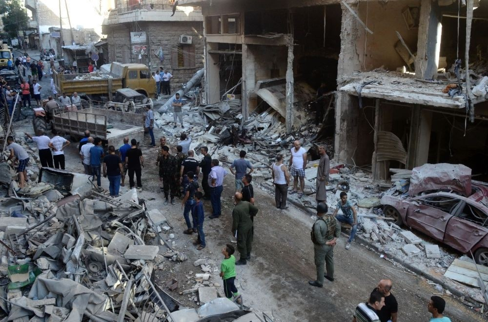 Syrians looking at the damage in a street in the ancient Syriac Quarter of the regime-held area of the northern Syrian city of Aleppo, July 11, 2016.