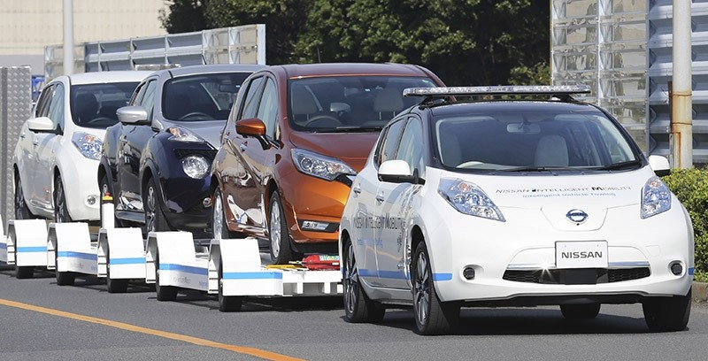 Nissan Motor Co.'S ,Leaf,, with no one inside, pulls a trailer with three other Leafs on it, during a demonstration of the automaker's Intelligent Vehicle Towing system at Nissan Oppama plant in Yokohama, Dec. 5, 2016. (AP Photo)