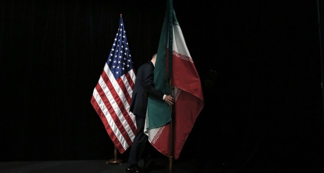A staff member removes the Iranian flag from the stage after a group picture with foreign ministers and representatives of United States and P5 countries has taken during the Iran nuclear talks at the Vienna International Center in Vienna.
