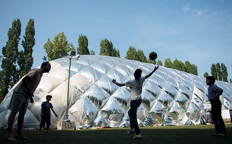 Migrant boys play soccer in front of an emergency accommodation shelter in a big air-inflated tent for asylum applicants in Berlin, Germany (Reuters Photo)