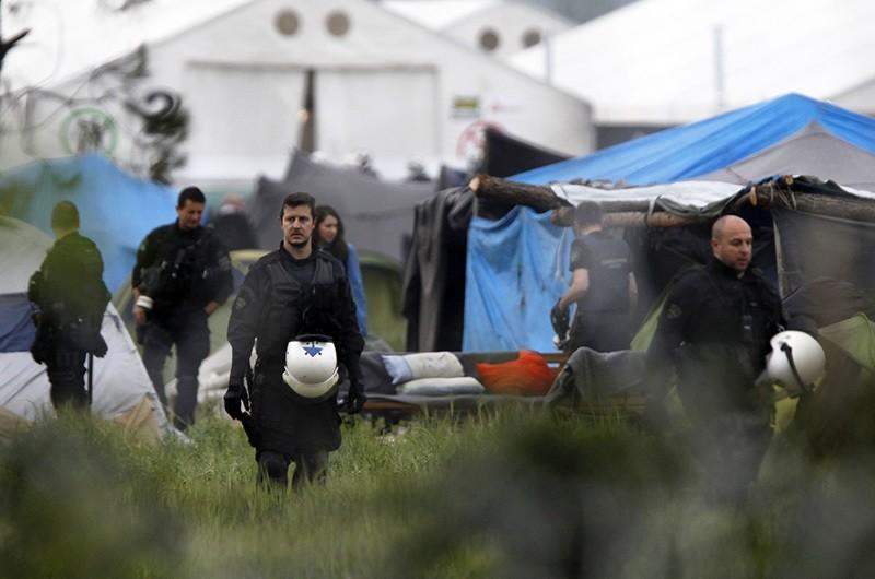 Greek policemen inspect the tents at a makeshift refugee camp at the Greek-Macedonian border near the northern village of Idomeni, Tuesday, May 24, 2016. (AP Photo)