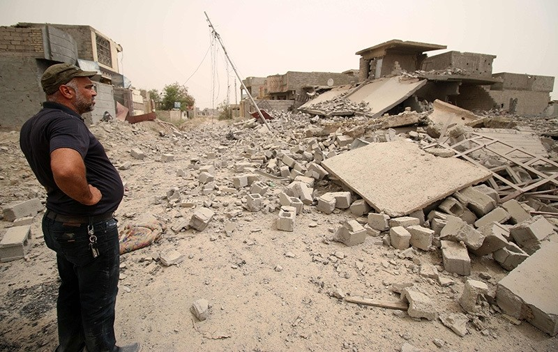 A member of the Iraqi counter terrorism forces inspects collapsed buildings in Fallujah's southern Shuhada neighbourhood after Iraqi govu2019t forces retook the area from Daesh on June 18, 2016 (AFP Photo)