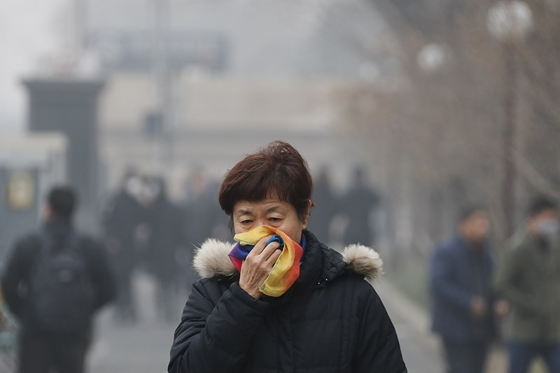 A woman uses a scarf to cover her mouth for protection against the air pollution as she walks on a street in Beijing, China in Dec. 2016. (AP file photo)