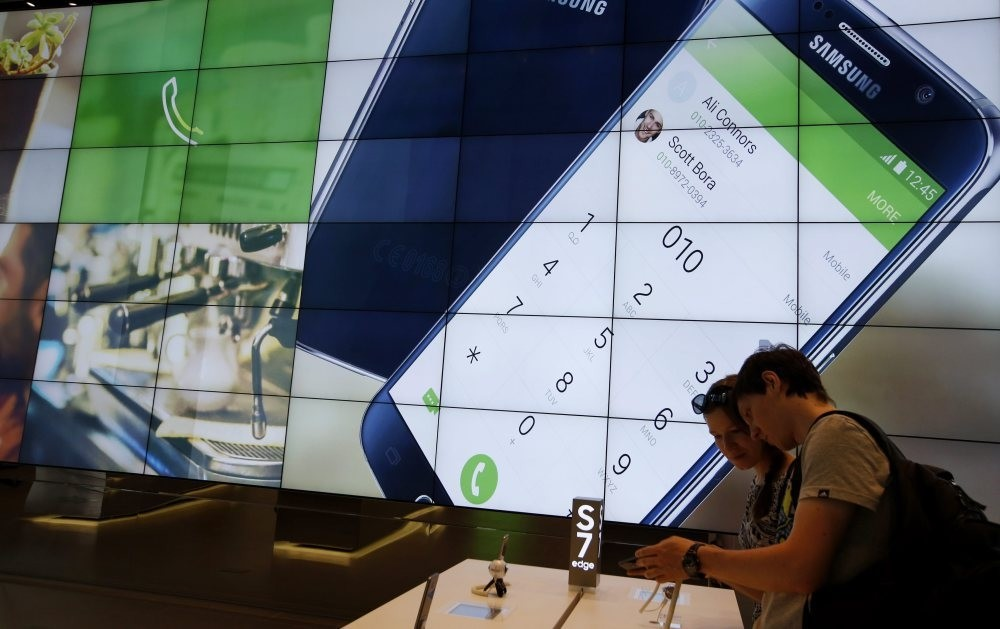 Foreign visitors look at a Samsung Galaxy S7 and a Galaxy S7 Edge smartphones in a showroom at the SamsungElectronics headquarters in Seoul. (EPA Photo)